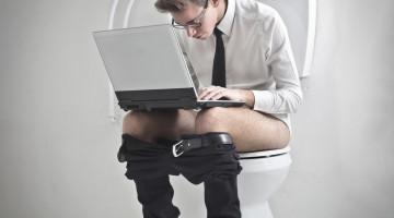 Ung mand på toilet med computer