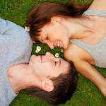 To unge mennesker ligger på en græsplæne og kigger på hinanden