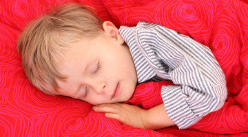 Lille dreng i stribet pyjamas sover